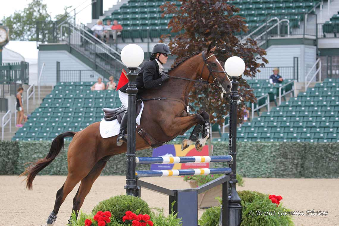 Autumn Schweiss going over a jump with her horse during the show jumping phase